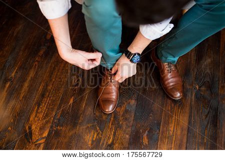 The groom ties the shoelaces in his brown shoes.