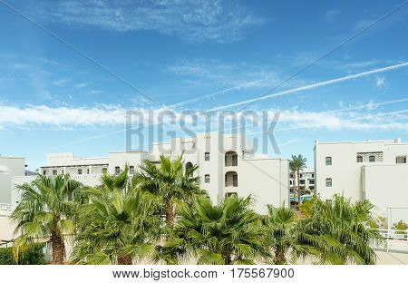 View at palm trees and a hotel foreside with blue sky and clods over it. Resort in Egypt