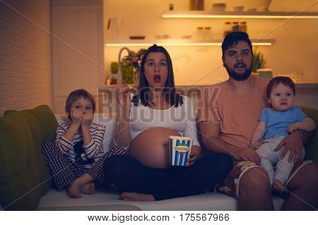 amazed family watching evening movie together at home