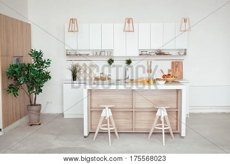 interior of small white kitchen with fresh fruit, two glasses of orange juice, baguette, red caviar, croissant and cookies with chocolate chips on the table.