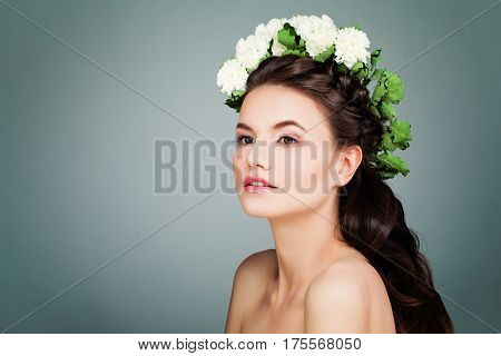 Cute Brunette Model Woman with Prom Hairstyle Makeup and White Flowers on Blue Background