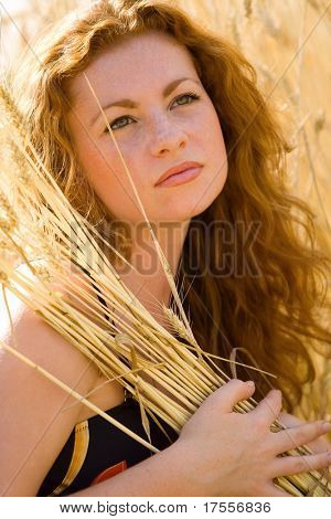 Red-haired young woman standing in wheat field