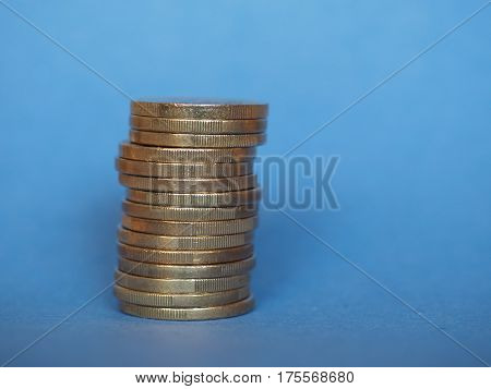 Pile of One Euro coins money (EUR) currency of European Union over blue background with copy space