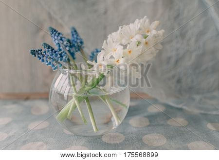 On the table a round glass vase with white hyacinth