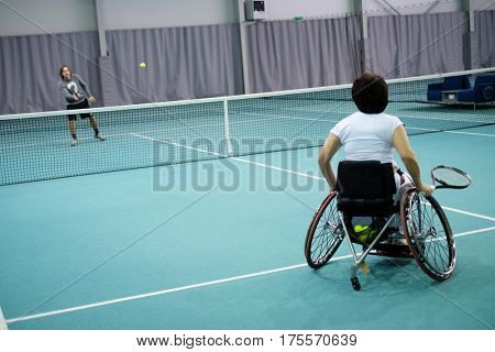 Disabled mature woman on wheelchair playing tennis with a coach