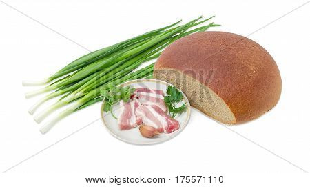 Several slices of uncooked streaky pork belly bacon garlic twigs of parsley and cilantro on dish partly incised hearth wheat and rye bread stalks of green onion on a light background