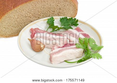 Several slices of uncooked streaky pork belly bacon garlic twigs of parsley and cilantro on saucer against the background of cut hearth brown bread closeup on a light background