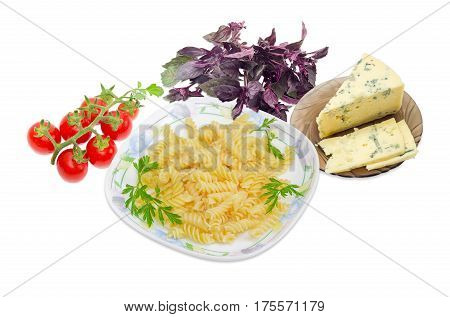Cooked spiral pasta and the parsley twigs on a dish cluster of the red cherry tomatoes blue cheese on a glass saucer and bundle of the purple basil on a light background