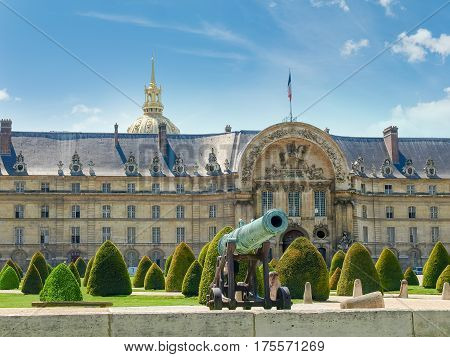 Part of the northern facade of the Hotel Des Invalides with archway of a main entrance with low-relief of King of France Louis XIV bronze cannon and garden in the foreground in Paris