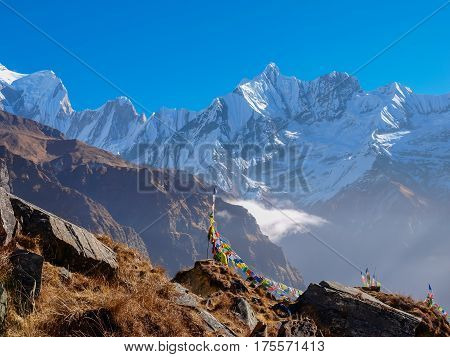 Mountain ranges with peaks covered with glaciers with rocky outcrops with withered grass and prayer flags in the foreground against the backdrop of the sky in the morning in the Himalayas
