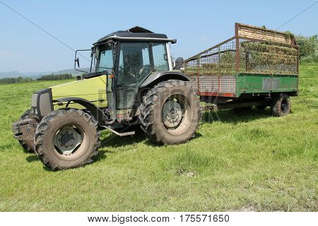 A Tractor with a Grass Collector Trailer at a Farm.