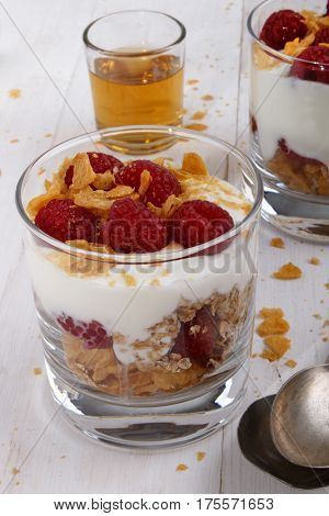 traditional cranachan with raspberry whipped cream and cornflakes in a glass