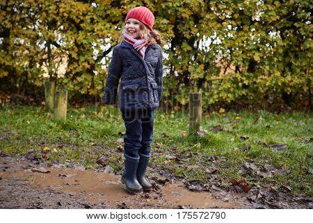Girl Splashing In Puddle On Winter Walk