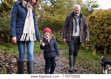 Multi Generation Family Take Dog For Walk In Fall Landscape