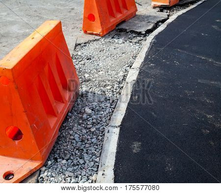 Road construction. New asphalt concrete concrete curb and orange safety barriers on the road.