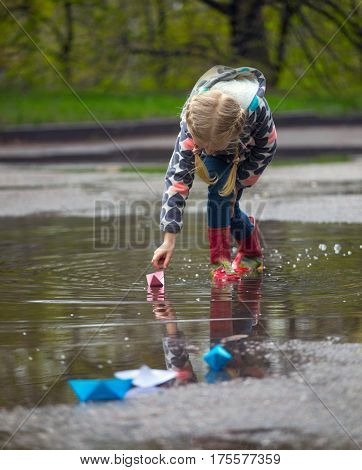 girl runs the pink paper boat in a puddle in the rain spring