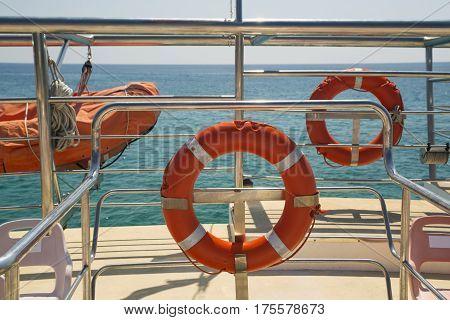 Life buoys on a yacht side. Concept of safe sea walk.