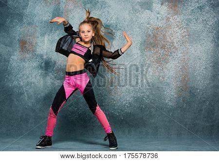 Young girl break dancing on gray wall stidio background.