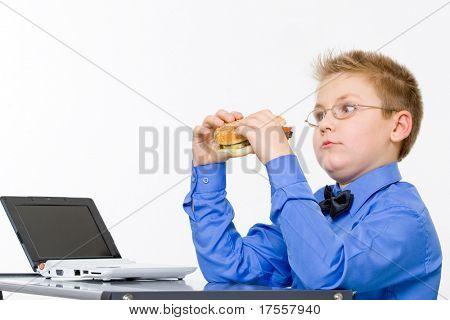 Young fat school boy eating hamburger