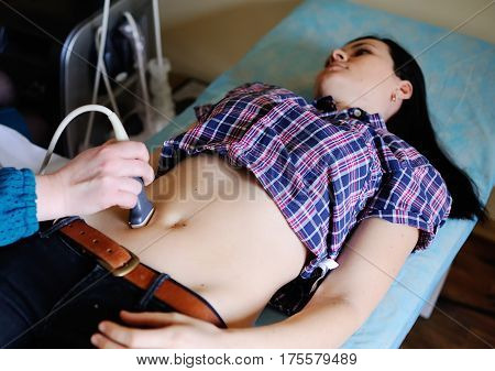 Doctor makes the patient women abdominal ultrasound. Pregnancy. Ultrasound Scanner in the hands of a doctor. Diagnostics. Sonography.