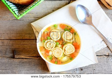 Vegetarian vegetable soup with omelette in a bowl, spoon on vintage wooden background with copy space for text. Homemade soup with omelette, carrot, peas, leek, cauliflower and potatoes. Top view