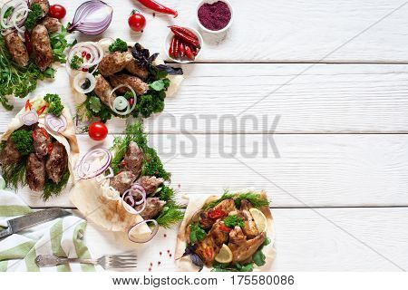 Grilled meat meals on white wooden table. Assortment on hot barbecue food assortment, free space. Restaurant menu, gourmet, lunch time concept