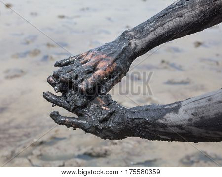 Smearing black healing mud on the body. Woman's hands. Close-up.