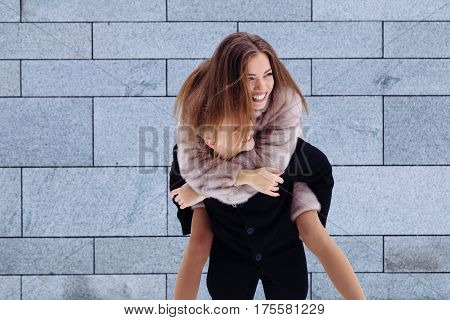 Portrait of a handsome man piggybacking his girlfriend on a vacation. Relationship concept.