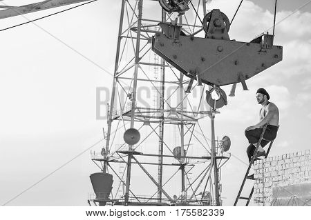 Old fashioned builder. Thoughtful retro styled handy man resting on top of the ladder at the building under construction industry crane worker profession job monochrome fearless high concept copyspace