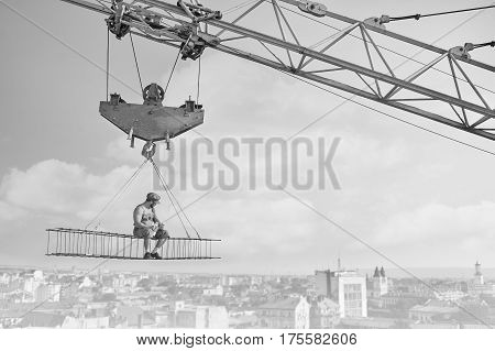 Perfect lunch. Monochrome shot of a shirtless retro builder enjoying peaceful lunch sitting on a crossbar high above the city construction crane building vintage black and white concept copyspace