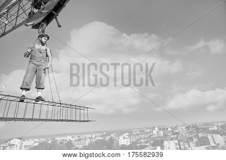 Not scared of heights. Black and white shot of a retro builder standing on a crossbar at construction site looking away thoughtfully toward copy space. high city professional worker industry engineer concept.
