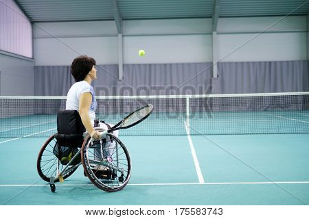 Disabled mature woman on wheelchair playing tennis on tennis court.