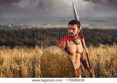 Lonely warrior. Handsome young Spartan warrior with a spear and a shield looking away thoughtfully standing in the field with copy space. Strength athleticism masculinity confidence concept.