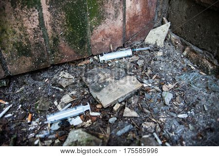 Syringes used by drug addicts in the garbage pile on the ground.