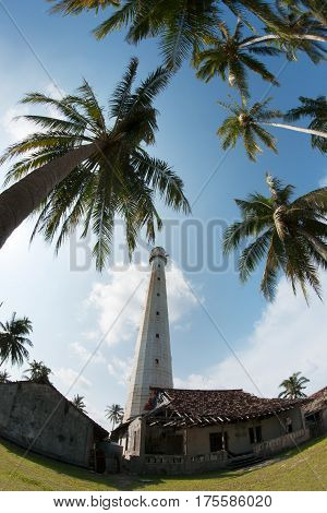 White lighthouse standing on an island with some green palm trees in Belitung at daytime with no people around.