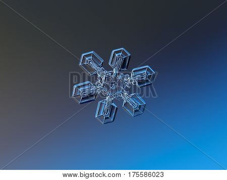 Macro photo of real snowflake: medium size snow crystal (around 4 millimeters from tip to tip) with simple, straight and broad arms, glittering on dark blue gradient background.