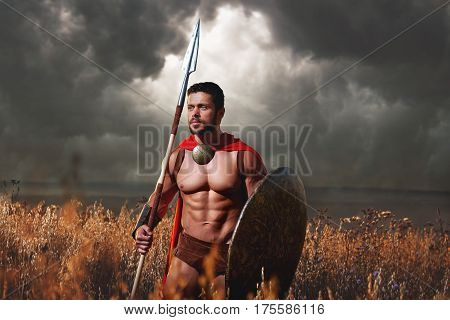 Handsome and powerful young muscular male warrior holding a spear and a shield standing alone under gloomy sky looking away. Masculinity strength power protector fighter concept.