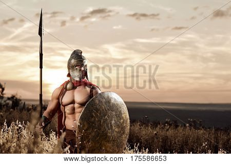 Fearless soldier. Sepia toned shot of a muscular powerful Roman soldier wearing a helmet and a cape holding a spear and a shield standing in the field looking away copy space. warrior fighter concept.