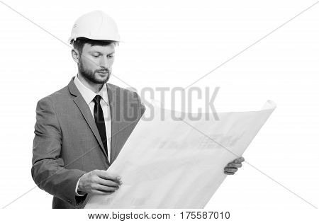 Professional architect. Black and white shot of serious bearded male architect in hardhat examining architectural blueprints isolated on white. Professional career occupation project new future concept.
