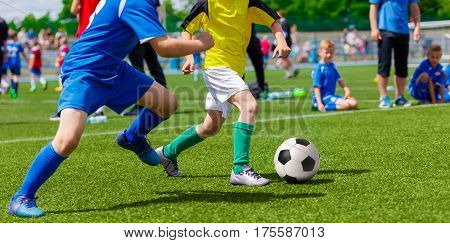 Young Boys Kids Children Playing Football Soccer Game. Running Soccer Players in Blue and Yellow Uniforms. Boys Kicking Soccer Ball