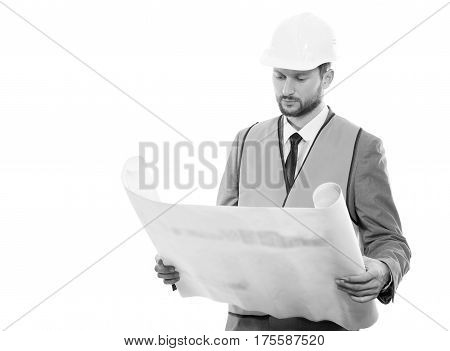 Final check. Black and white shot of a confident successful male constructionist in a hardhat and safety vest looking at the blueprints on white background with copyspace