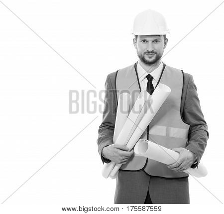 Developing business. Vertical studio portrait of a cheerful male engineer in a hardhat and safety vest posing on white background holding architectural blueprints smiling to the camera
