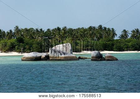 Natural rock formation in sea at Belitung Island in the afternoon and a white sand beach with green palm trees at the background Indonesia.