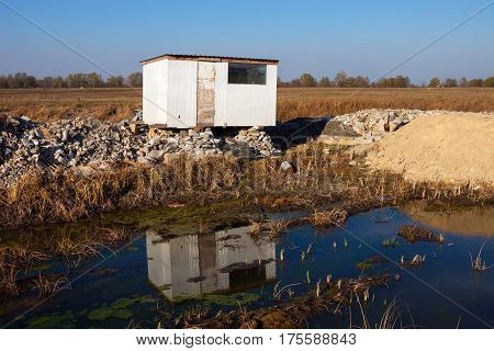 Old abandoned white plastic shed near the mud.