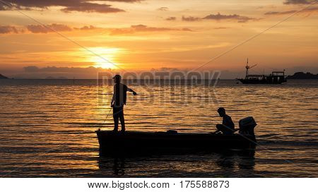 Silhouette of two fishermen on a small fishing boat with outboard motor on the ocean at nightfall with an orange sunset at the background in asia.