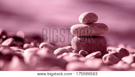 Website banner of Zen balancing pebbles on the beach in pink