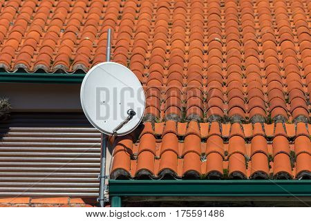 satellite dish on the background on the roof tiles