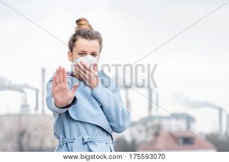 Young woman in protective mask suffering from air pollution from big manufacturing in the city
