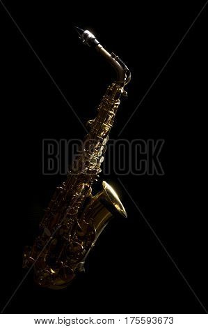 low key vintage alto saxophone and light in the dark background