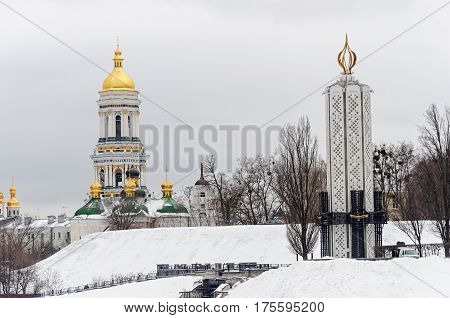 Winter view of Kiev-Pechersk Lavra and Holodomor monument with National Museum
